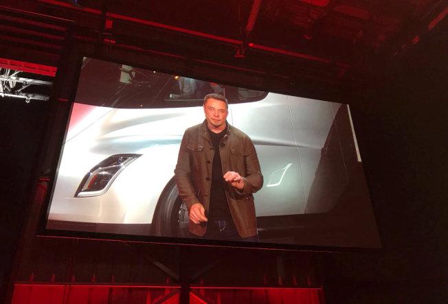 展示會現場大型屏幕顯示,特斯拉執行長站在全電動貨櫃車前面。(路透)
