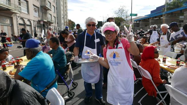 Midnight Mission的亞裔志願者給遊民端菜。(記者李雪/攝影)