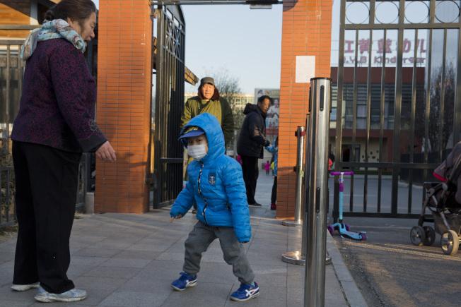 爆出虐童案的北京朝陽區新天地的紅黃藍幼兒園,24日當天家長在接幼兒回家。(美聯社)