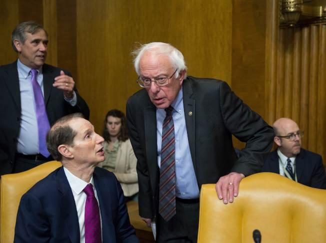民主黨籍參議員魏登(前左)、桑德斯(中)在國會參院委員會發言反對共和黨版稅改。(Getty Images)