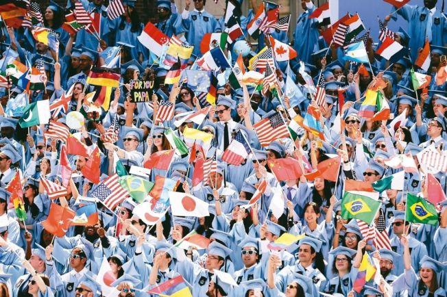 紐約哥倫比亞大學國際事務學院的國際學生在畢業典禮上揮舞本國國旗。 美聯社