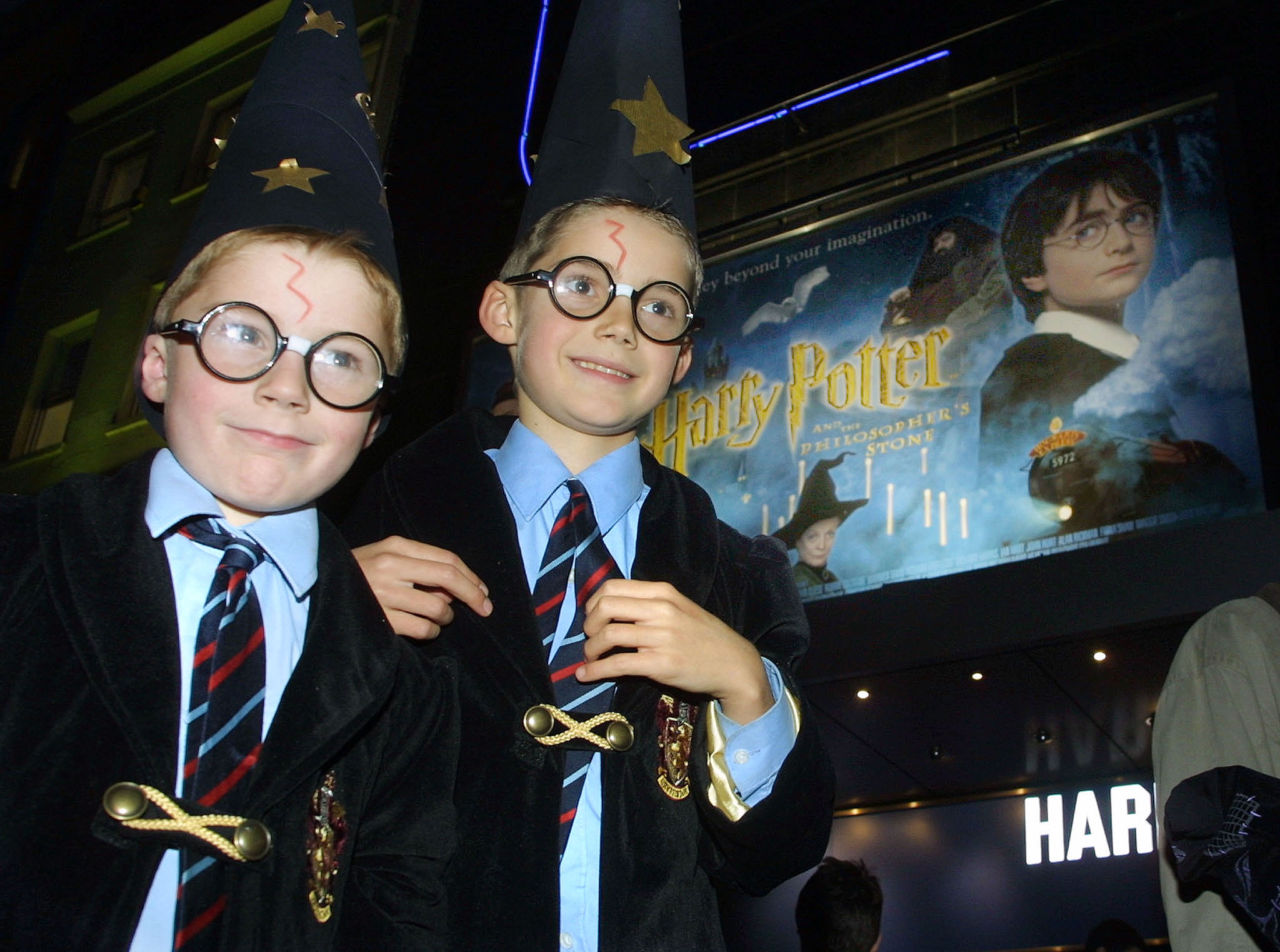2001年11月16日,兩位小小哈利波特迷在倫敦一家戲院外盛裝打扮、等著看電影首映。(美聯社)