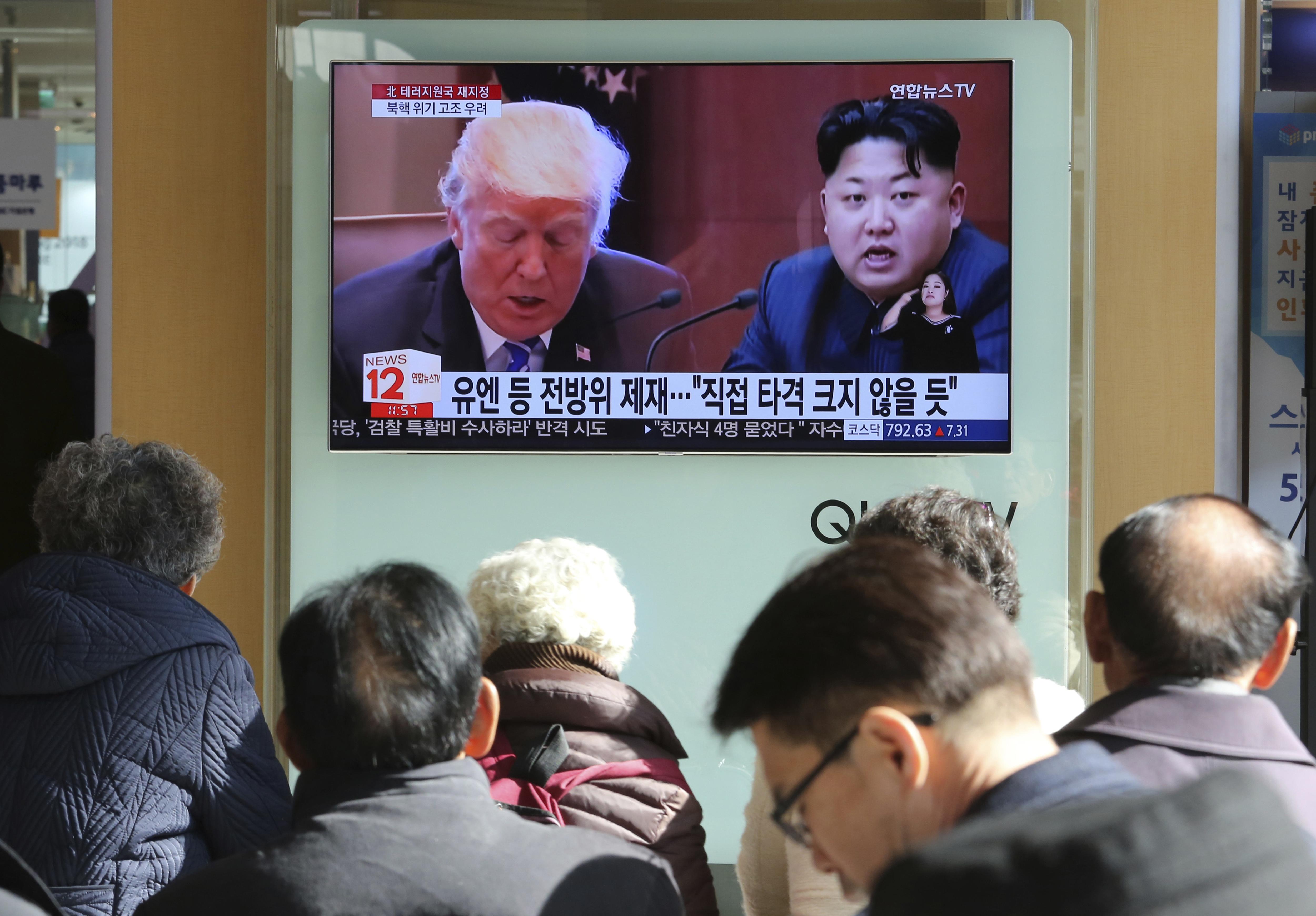 南韓首爾車站的大電視螢幕前,21日有民眾圍觀美國總統川普(左)宣布加強制裁北韓的新聞,與川普並列的是北韓領導人金正恩。 美聯社