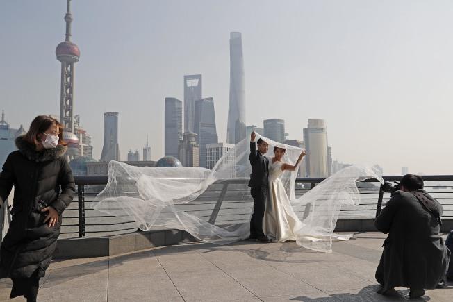 一對準新人在上海外灘濱江步道上拍攝婚紗照。(中新社)