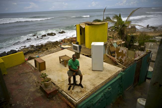 颶風瑪麗亞席捲波多黎各後,拉佩拉(La Perla)一位居民坐在被毀家中的桌子上。今年的颶風季終於結束。(美聯社)