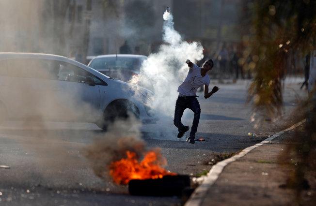 一旦美國宣布耶路撒冷作以色列首都,將激怒巴人和觸發更激烈抗爭。圖為巴勒斯坦示威者11月30日在約旦河西岸納布盧斯擲回以色列軍施放的催淚彈。(路透)