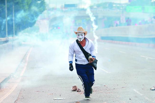 宏都拉斯候選人納斯拉亞支持者戴V怪客面具,在街頭放煙霧彈。 (路透)