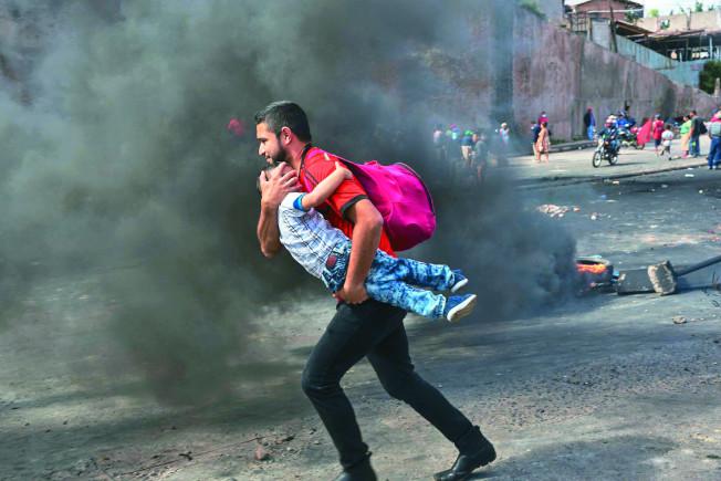德古西加巴群眾示威;一位父親抱稚子穿越冒著黑煙的街道。(美聯社)