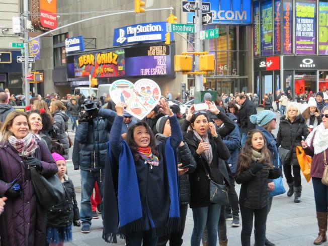 紐約時報廣場及台北Sogo復興館前,兩端民眾透過電視牆連線,跨洋以手勢比愛心。(記者陳小寧/攝影)