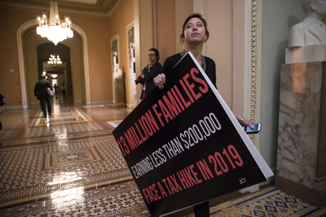 民主黨參議員魏登的助理攜帶一塊大型反對標語走進議場。(美聯社)