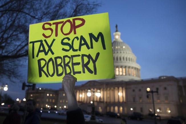 反對稅改案的民眾,在國會外舉牌抗議。(歐新社)