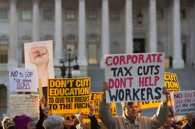 反對稅改案的民眾,在國會外舉牌抗議。(Getty Images)