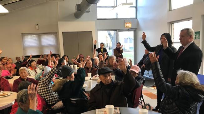 伊州參議員德賓(立者右一)在華埠詢問有多少耆老為入籍公民,並鼓勵大家踴躍投票表達民意,共同挽救社福項目遭砍的局勢。(特派員黃惠玲/攝影)