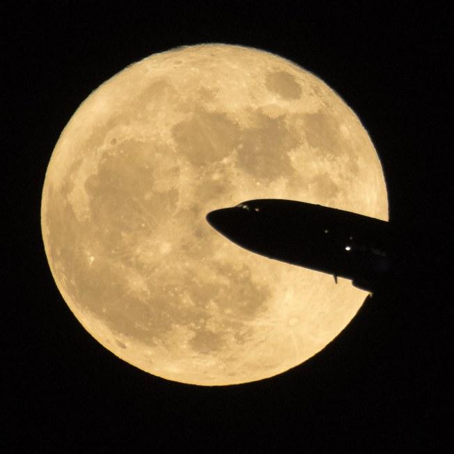 自美國華府雷根國際機場起飛的航機,背景是超級大月亮。(歐新社)