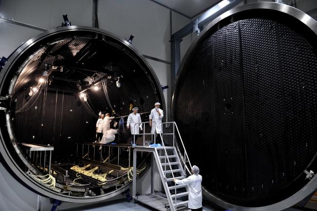 工作人員在中科院微小衛星創新研究院的衛星環境模擬實驗裝置裏工作。(新華社)