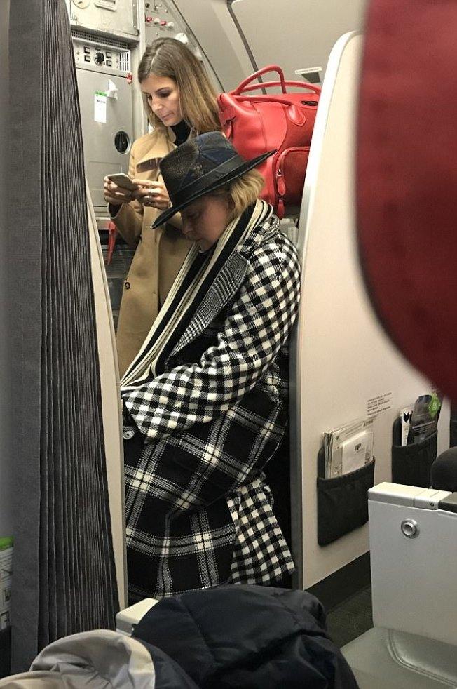 瑪丹娜(前)頂著素顏與助理搭葡萄牙航空經濟艙,被拍到靠著行李箱休息。(取材自英國每日郵報)