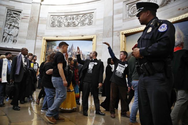 「貧窮者活動」組織抗議群眾4日在國會大廈抗議共和黨的稅改法案。(美聯社)