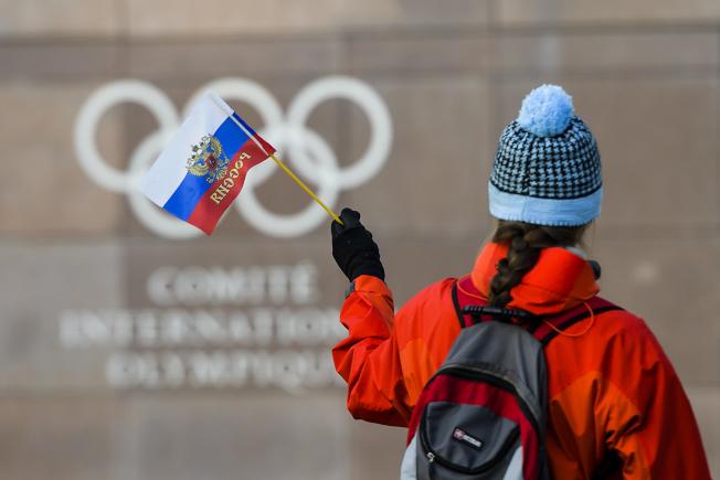 在瑞士洛桑的國際奧會總部前面,一名婦女對著五環揮舞俄羅斯國旗。(美聯社)