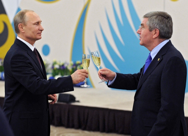 俄羅斯總統普亭(左)與國際奧會主席巴赫在索契冬奧會舉杯。(美聯社)