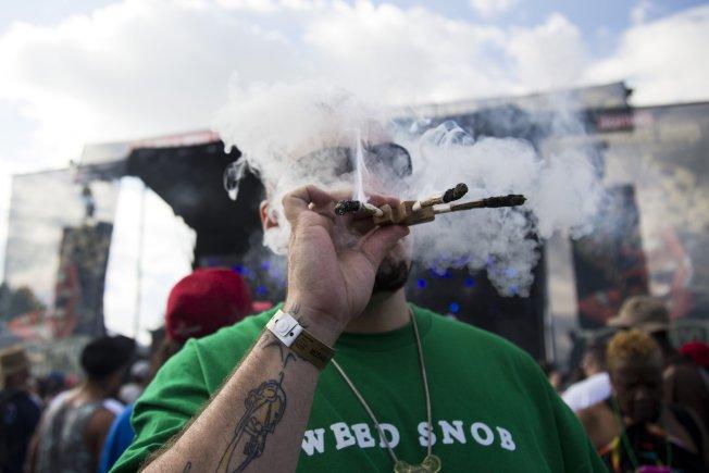 圖為今年6月,一名男子在密西根州克里歐中西部高峰大麻盃活動上吸食大麻。(美聯社)
