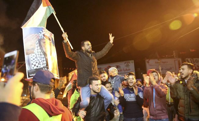 巴勒斯坦抗議民眾揮舞國旗及前領導人阿拉法特的相片。(美聯社)