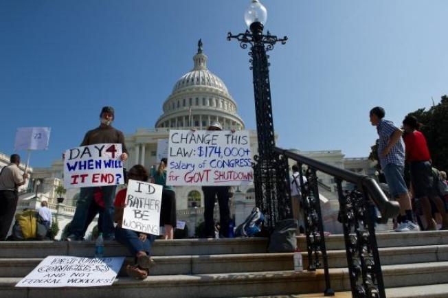 2013年聯邦政府關閉,政府雇員在國會前舉牌要求早日回去工作。(Getty Images)