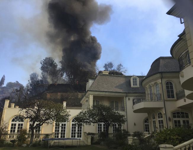 貝萊爾豪宅後面山坡冒出濃煙,居民倉皇逃走。(美聯社)