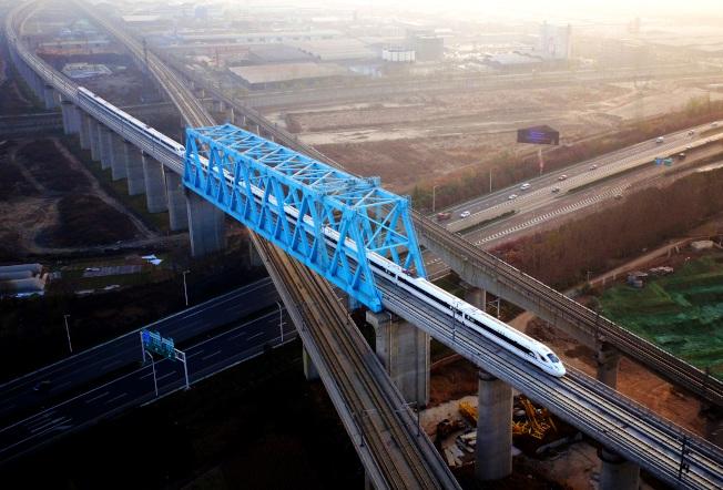 西成高鐵由西安北站駛出的列車,經過西成高鐵跨西寶高鐵特大橋。(新華社)