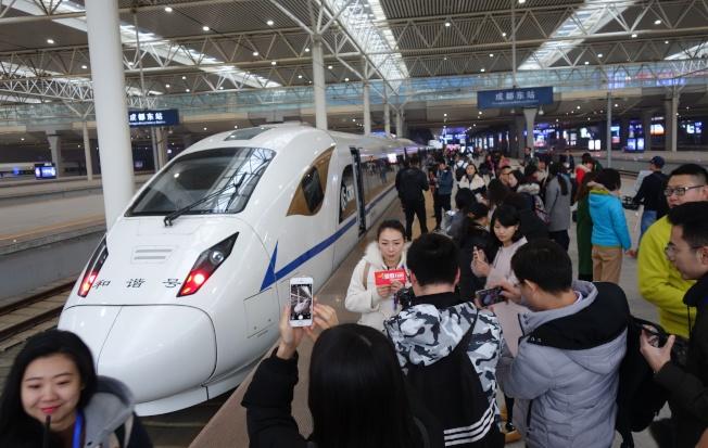 隨著兩列CRH3A型動車組從成都、西安兩地對發,西成高鐵正式通車。圖為即將發車的成都至西安首發列車吸引媒體。(中新社)