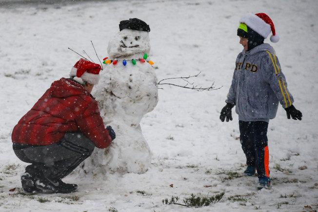 孩子們在紐約曼哈頓中央公園堆雪人。(路透)