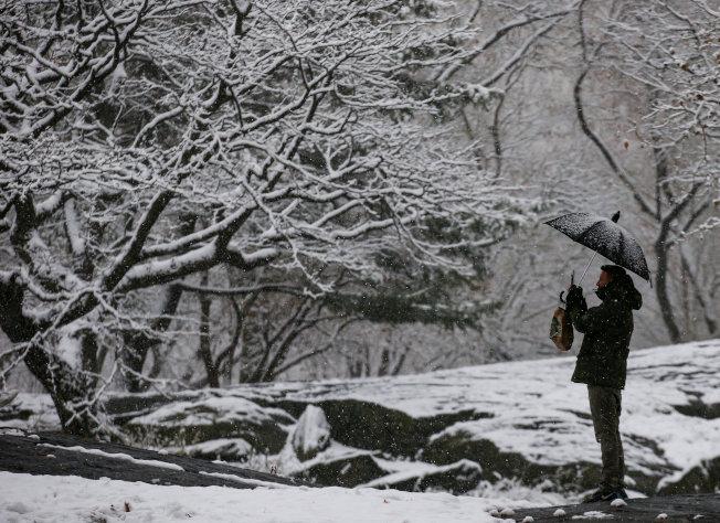 紐約白色的雪景,吸引路人攝取美景。(路透)