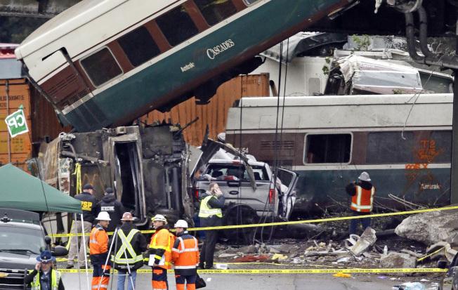 脫軌翻覆的列車嚴重損壞,現場救難人員持續搜救中。(美聯社)