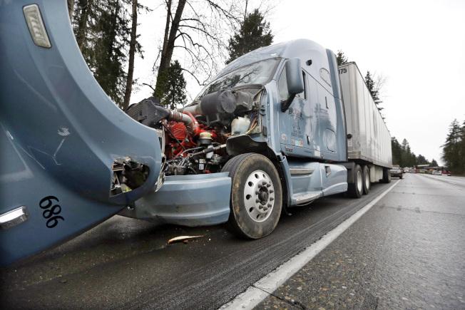火車掉落到州際公路上壓壞許多車輛,幸好車主都只有受傷,無生命危險。(美聯社)