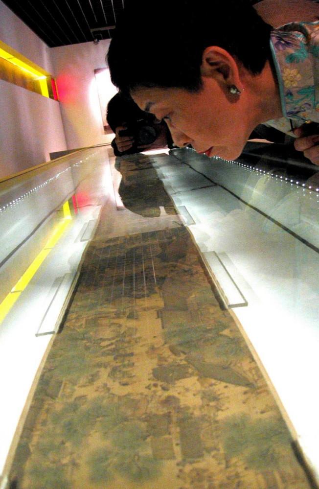一位遊客在北京故宮博物院仔細觀賞展櫃中的真本《清明上河圖》。(新華社資料照片)