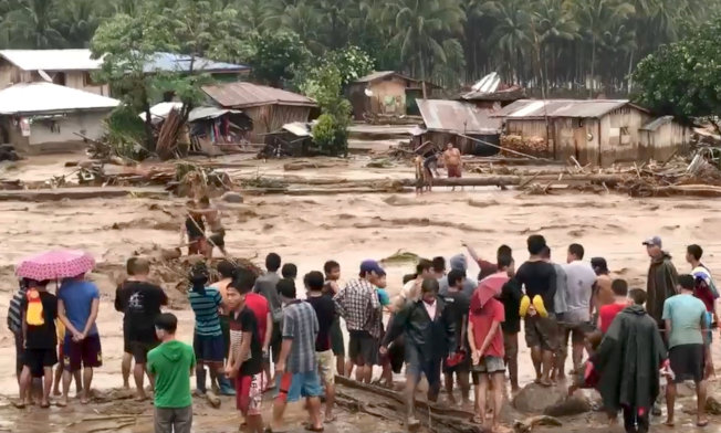 天秤颱風侵襲菲律賓民答那峨島,豪雨引發洪水,民眾協力渡過滾滾洪流。(路透)