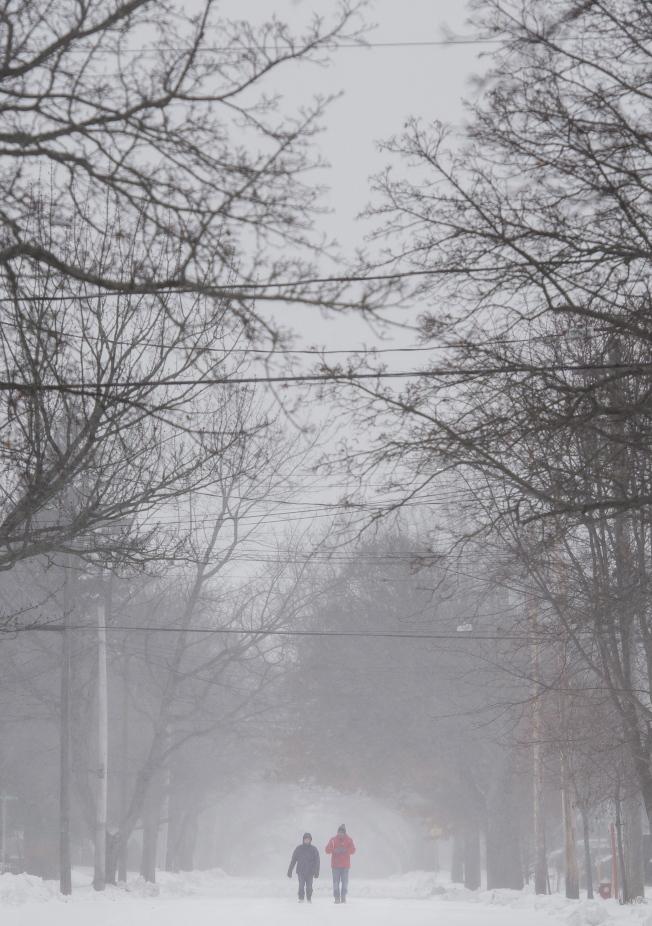 白色聖誕節/加拿大東部、臨近大西洋的New Brunswick,周一下雪,行人走過Moncton市區積雪的道路上。 (美聯社)