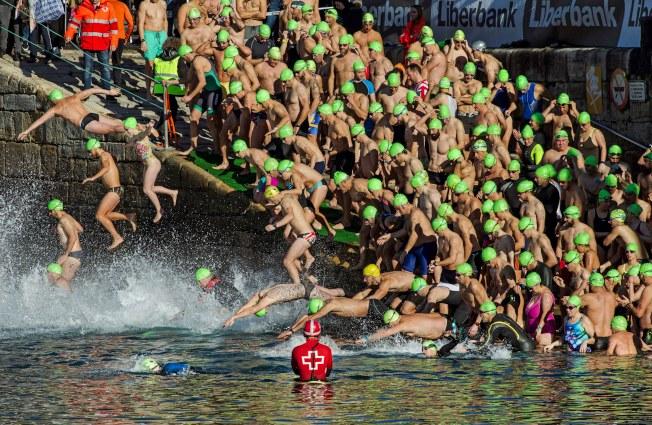 泳度聖誕節/西班牙古老傳統的聖誕游泳競賽,游泳選手們在港口的碼頭邊爭相跳水,想贏得這場 200米的水中競賽。(歐新社)