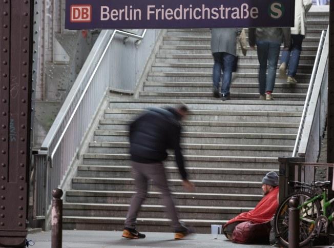 分享聖誕節/德國柏林的 Friedrichstrasse車站,路過的行人投了銅板給坐在樓梯口的無家可歸者。教宗方救濟各在聖誕文告中呼籲包容移民難民,別讓任何人覺得他們「在地球上無容身之地」。(歐新社)