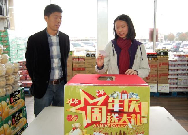 惠康超市負責人Robret(左)邀請現場顧客抽獎。(記者賈忠╱攝影)