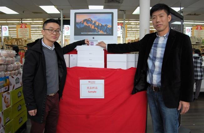 惠康超市負責人Robret(右)與抽出一等獎的顧客共同展示獲獎號碼。(記者賈忠╱攝影)