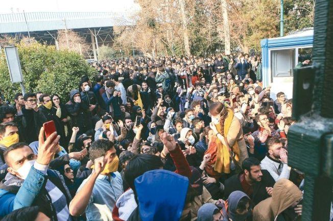伊朗反政府抗議潮從街頭延燒至校園,大批學生12月30日想進入德黑蘭大學校園參加示威,遭鎮暴警察阻攔。 (美聯社)