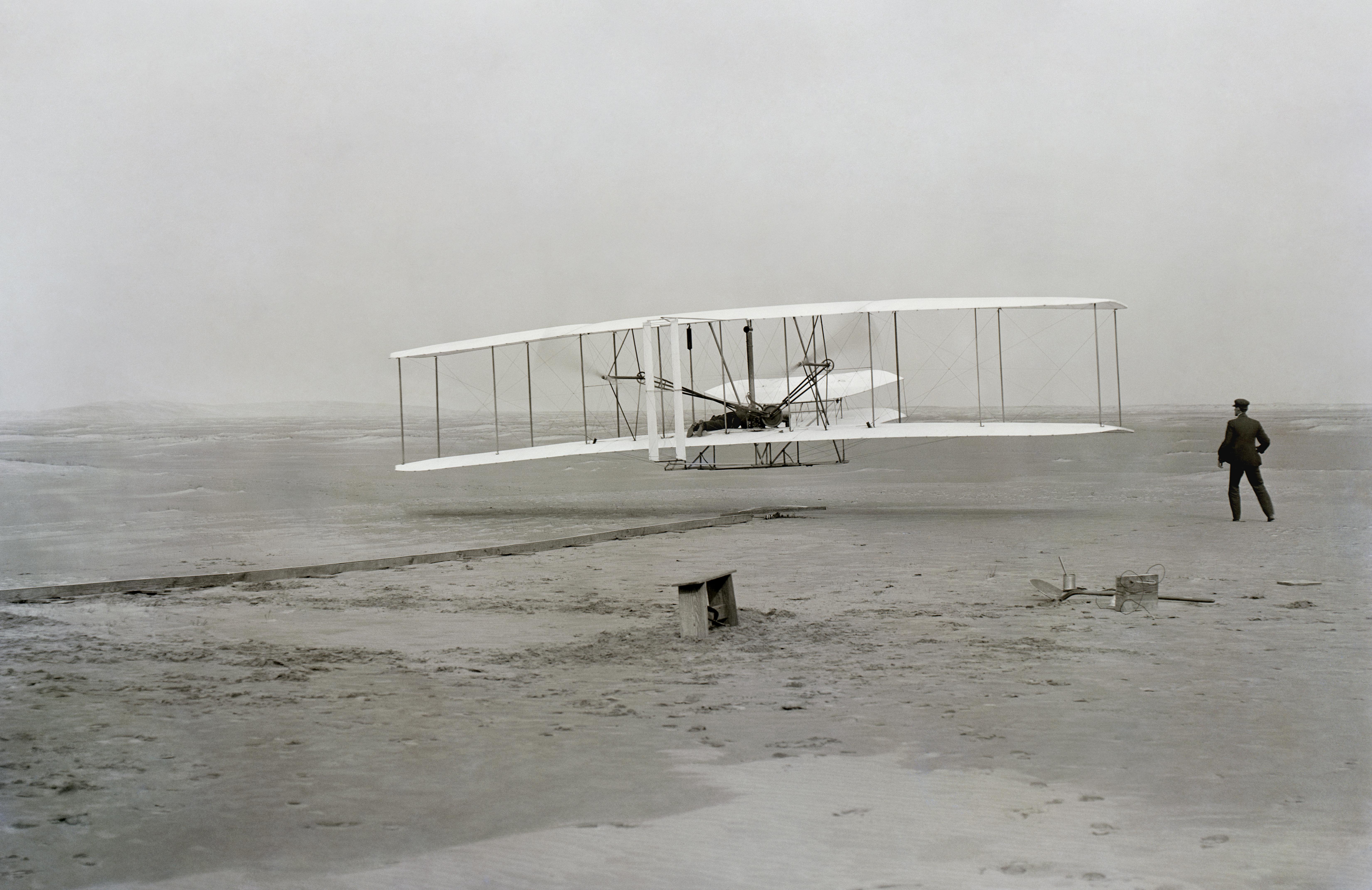 萊特兄弟飛行者一號的首次飛行。攝於1903年12月17日。奧維爾擔任駕駛員,威爾伯在翼尖處跟跑。(國會圖書館)
