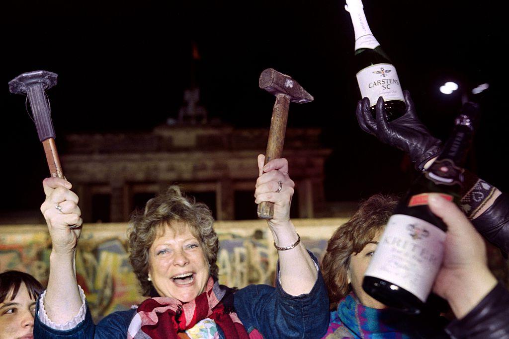1989年柏林圍牆倒下時所有人奔騰慶祝,一名女子手上還拿著槌子。(Getty Images)