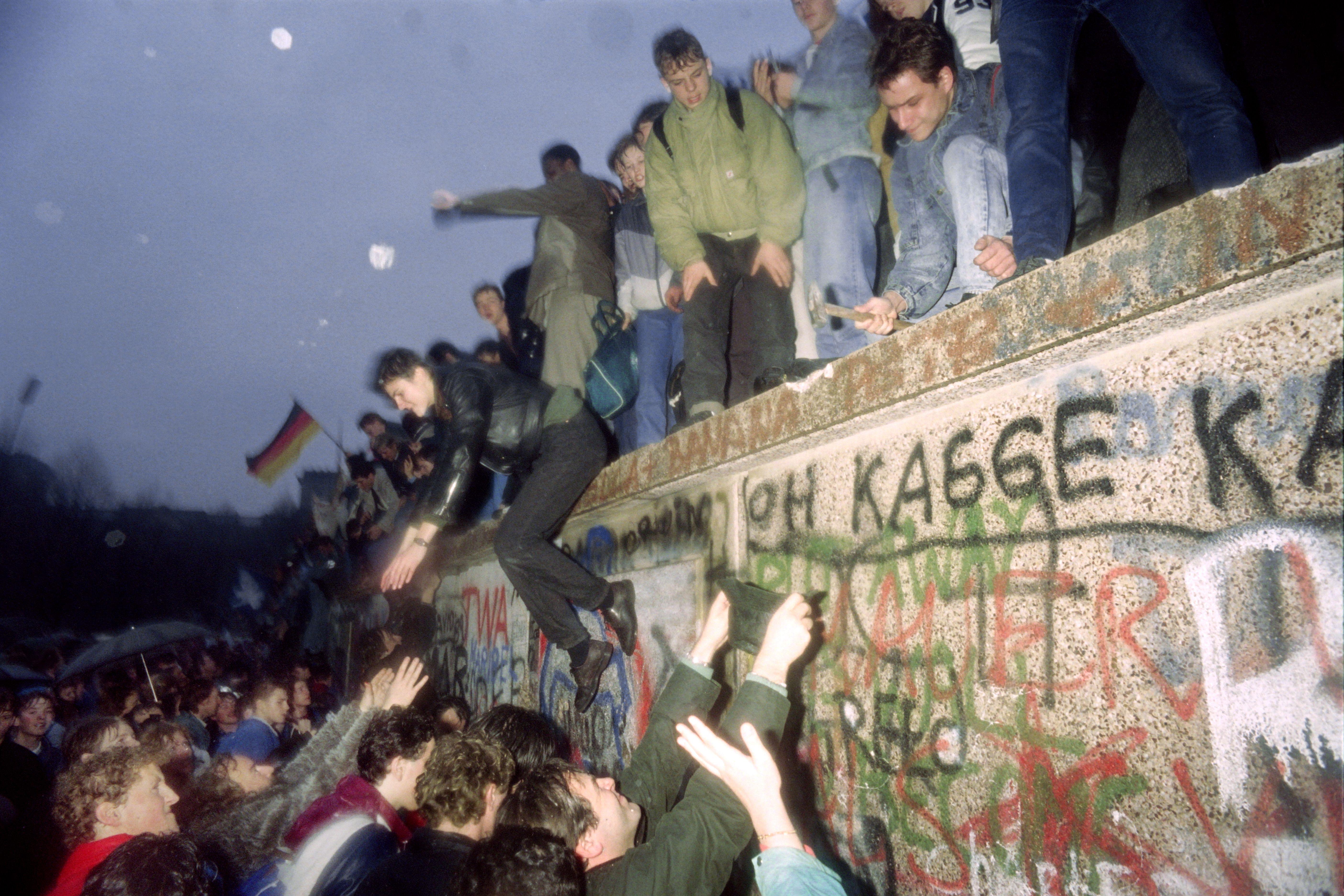 1989年11月10日清晨,東柏林人在翻越柏林圍牆時得到了西柏林人的幫助。(Getty Images)