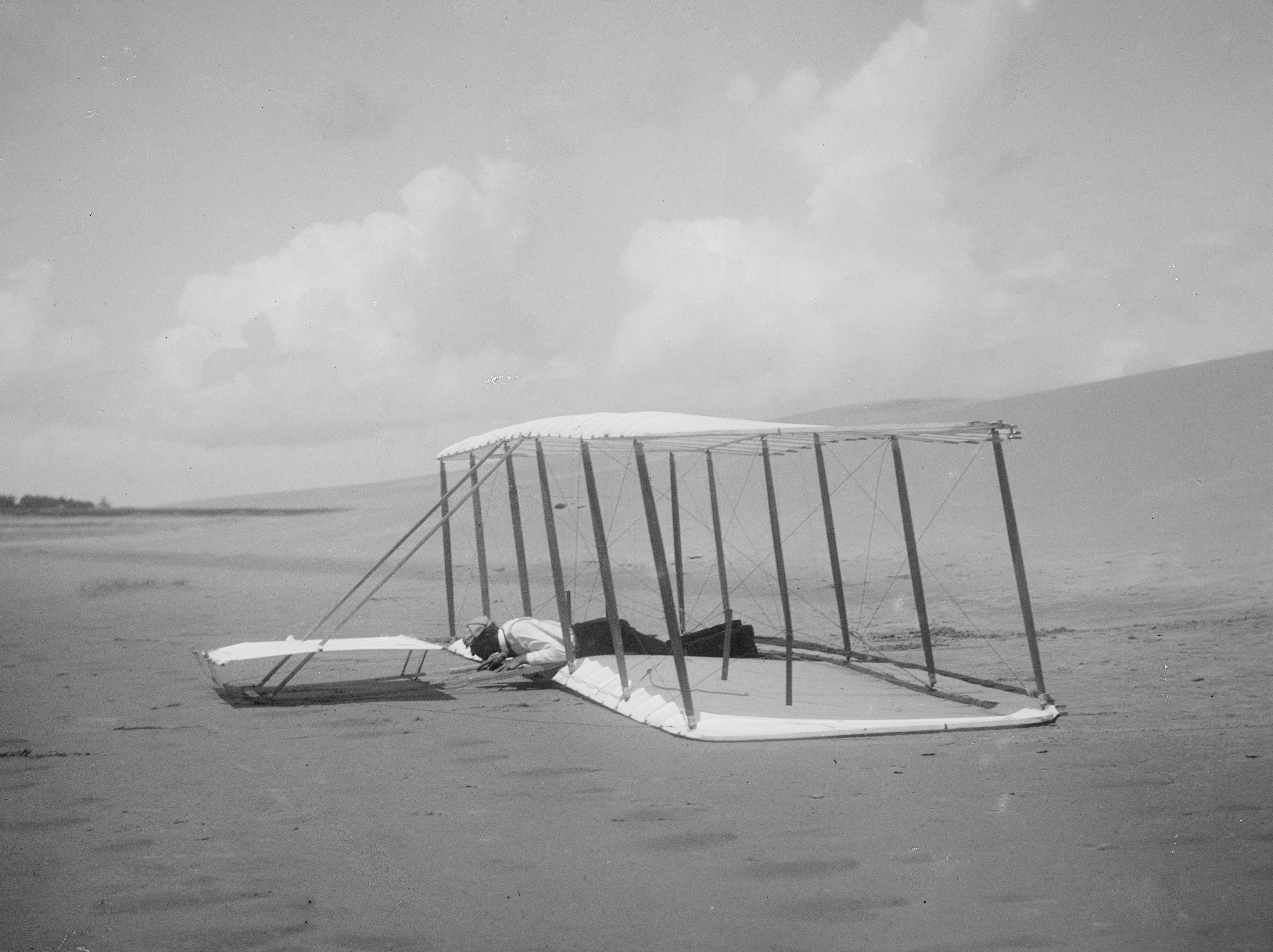 剛剛駕駛1901年滑翔機著陸的威爾伯。機身後方拖著降落時的劃痕,畫面前方的痕跡是之前幾次試飛時留下的。(國會圖書館)