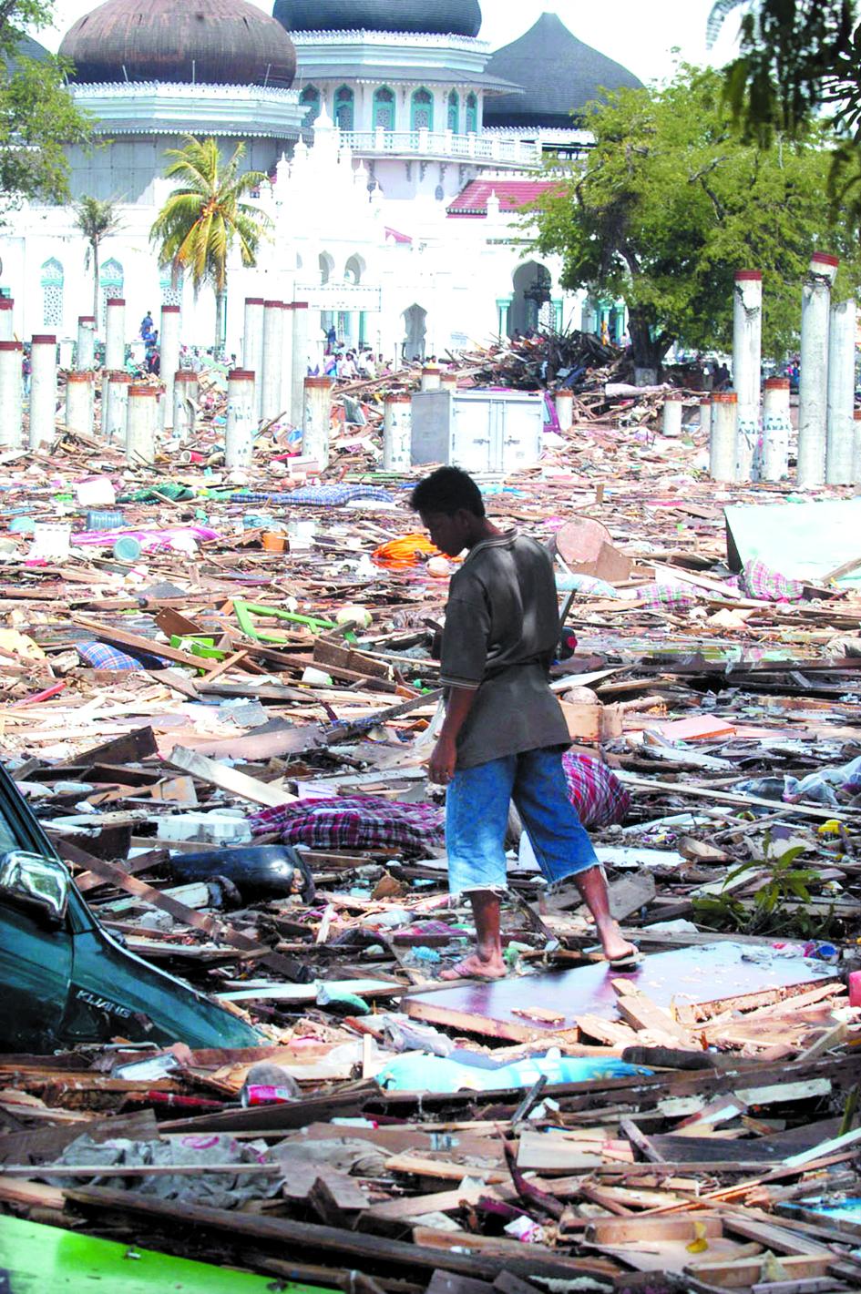 圖為印尼亞齊省班達亞齊市一名男子27日在被海嘯摧毀的建築瓦礫中行走,數十具鼓脹的屍體橫陳在街頭。美聯社
