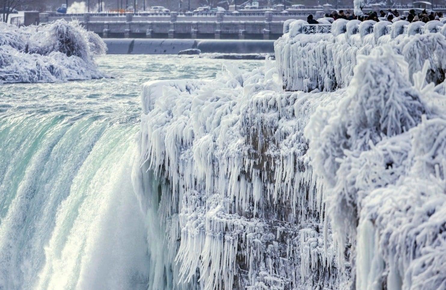 29日位於安大略省的尼加拉瀑布已結成冰柱,岸邊仍有許多旅客拍照留念。(美聯社)