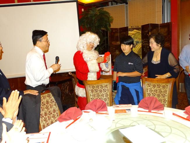前會長陳清諒(左二)扮聖誕老公公,發放紅包給小朋友。