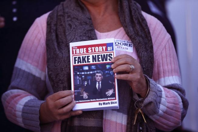 圖為一名共和黨支持者手持一本封面印有「假新聞」字樣的書。(美聯社)