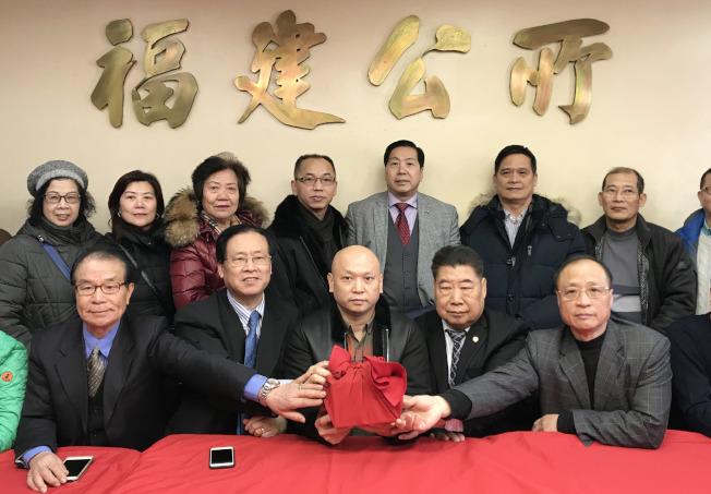 福建公所新舊主席交接,鄭德良(前排中)從鄭時甘(前排左二)手中接過印信。(記者俞姝含/攝影)